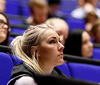 Lecture in a large lecture hall. Female student listening.