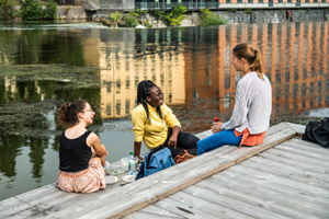 Three students who sit on a bridge talking to each other.