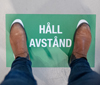 """Two feet standing on a sign saying """"Keep the distance""""."""