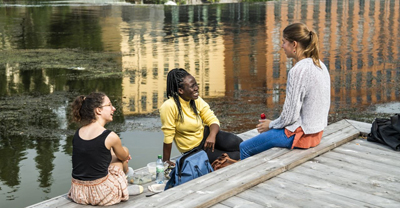 Three women sitting on an outdoor stairs by a river talking.