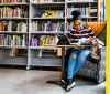 Female student in a chair and a book shelf with lots of books behind her.